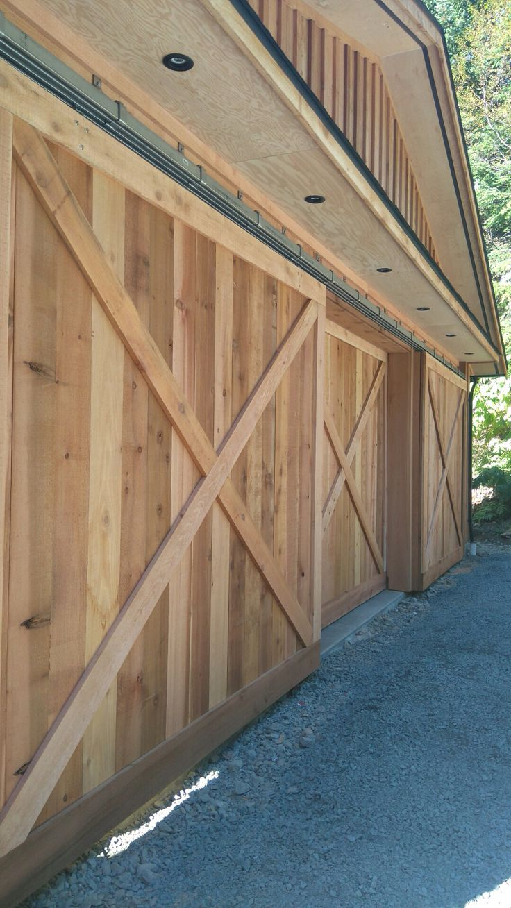 The cedar barn doors and track system. Two tracks outside and one inside allows me to have 2 doors open at once and minimizes door gap.  The tracks are galvanized steel with Stanley hangers/rollers. 99 feet total of track for our 33 foot span