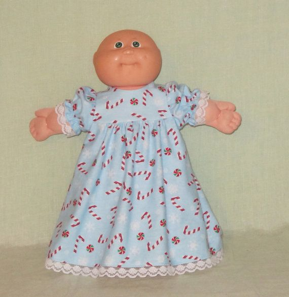 For Sale today is a nightgown that I have made to fit the American Girl Bitty Baby Doll, the 14 inch Cabbage Patch Doll, or other 14 to15 inch Baby Dolls.  The nightgown is made from a candy canes on blue print flannel. The bodice is lined and closes in the back with Velcro. It has lace on the short puffy sleeves and at the hem. My dolls and stands are not included in the sale. The sale is for the nightgown only. Thank you for looking at my items and please take a minute to browse my shop…
