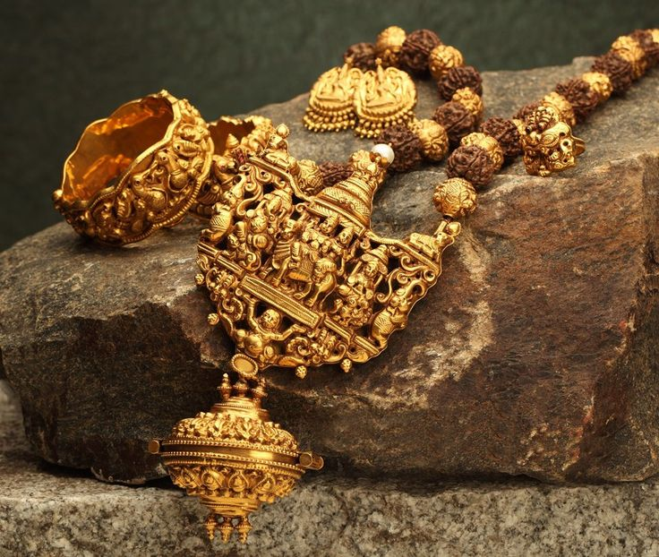 Chunky gold pendant in antique finish on a strand of rudraksh