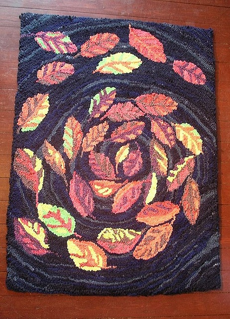 Rag Rug. Primitive hooked rag rug with design of swirling autumn leaves. The rug is made from about four blankets that have been dyed, before hooking onto a hessian backing using a speed shuttle hook.