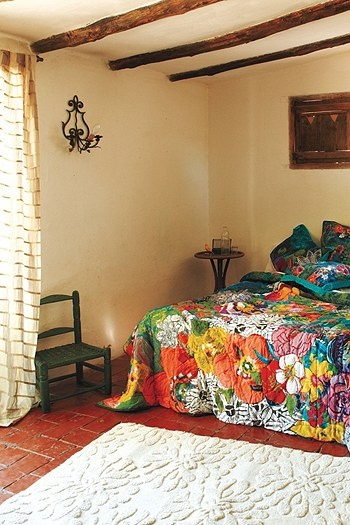 so gorgeous... that quilt, that rug, those beams, that sconce...