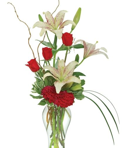 Lily Elegance-Three radiant red anniversary roses display their beauty with even more panache when presented in a vertical arrangement with a mix of anniversary lilies and red blooms. Send your love and with this dramatic floral gift. #Lilies #Flowers #GriffinsFloralDesign #ColumbusFlowers