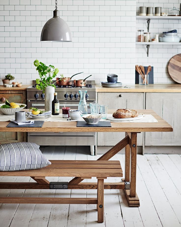 Gorgeous kitchen with white tiles, a wooden table and bench seats.