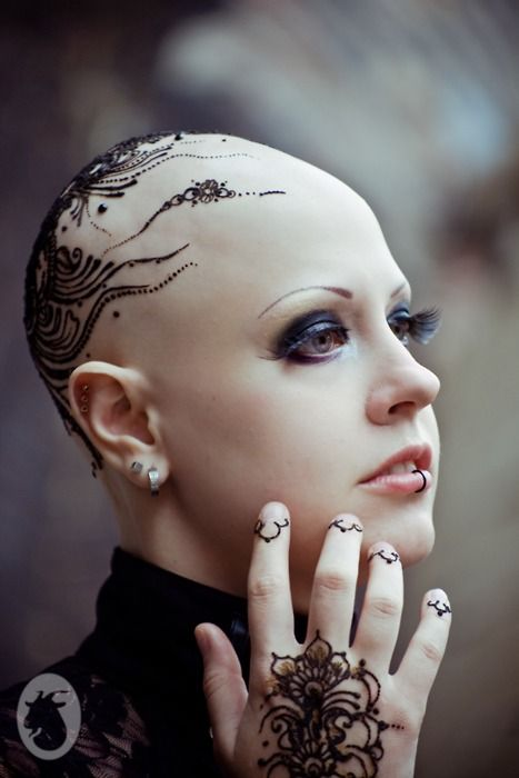 Tattoos and Piercings are close to Tat, but she would have natural eyebrows and no makeup, and probably even more ink.