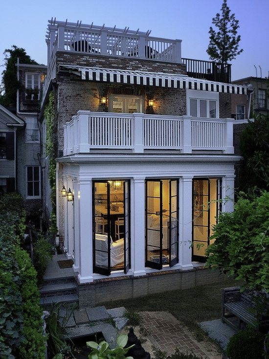 row house addition:  door sized windows open onto patio.