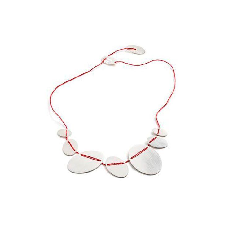 """Halskæde, """"Ovaler"""", af rød silkesnor med 7 ovaler af sølv og lås også af 2 sølvovaler - silkesnoren går igennem ovalerne. Smykkedesign: Karen Fly."""