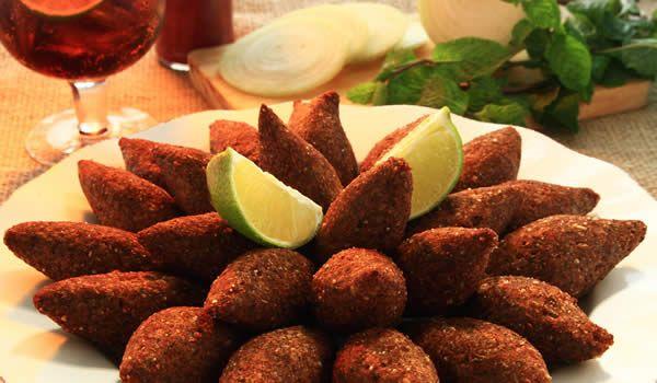 """O Quibe é um prato típico do Oriente Médio que consiste em um bolinho de massa de triguilho ou semolina, recheado com carne, temperada com ervas, que pode ser servido crú, cozido ou frito. O nome deriva de """"kubbeh"""" que em árabe significa """"bola""""."""