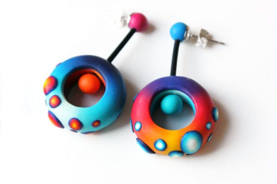 Funny and colorful polymer clay pieces linked to an earstud or a hook by means of a section of elastic neoprene cord with ball ends glued with Loctite Power Flex, a specific glue for elastic materials. Nido bead measurements in average: outer diameter: 25 mm, inner diameter: 13 mm. Height: 8 mm. These odd earrings can be made to order in any other measurements. You can also determine the color palette (see my suggestions), as well as the finish: hooks or earstuds. Handmade, exclusive design…