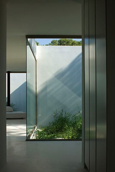 Glass walls and small patio, interior of the Ibicaelum House in Spain by Bruno…