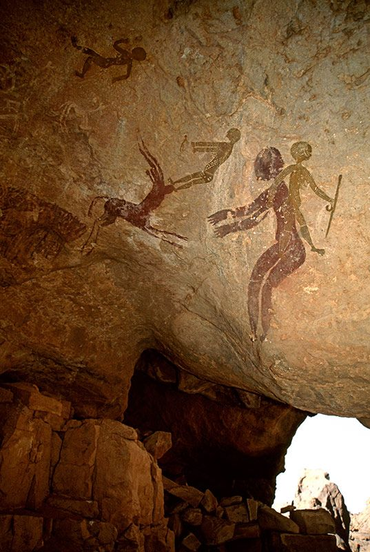 Djanet, Algérie. A droite, femme avec des seins et le corps bien décoré et les jambes, détient bâton, progrès droite, superposée à personne la tête baissée et les bras face à gauche.