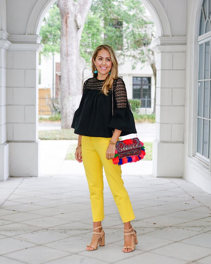 Black bell sleeve top, yellow pants, pom pom purse