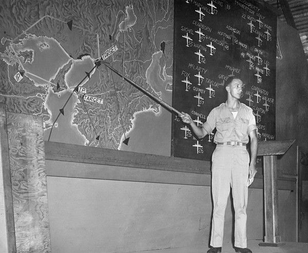 Planning a bombing raid on Japan from Saipan in the Marianas Islands. Capt. Glenn McClure, 500th Bombardment Group, 20th Air Force, pointing to targets on a map of Japan. The air raid's formations of B-29s are on the blackboard behind him. August 13, 1945, several days after the Atomic bombing of Japan, but before the Japanese Surrender.
