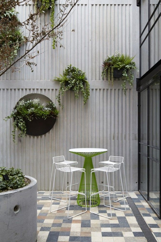 softening a corrugated metal wall with planters and interesting tiling. Prahran Hotel / Techne Architects