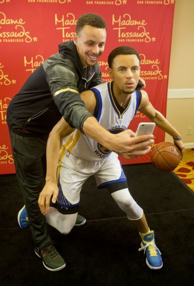 Golden State Warriors' Stephen Curry takes a selfie with his wax figure made by…