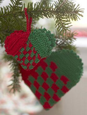 """De fine """"flettede"""" julehjerter er udført som tofarvet hækling, dvs. at man lader begge farver garn følges ad, men hækler hen over den tråd man ikke bruger."""