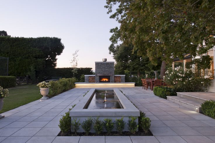 This large water feature is paired with an generous stone fireplace to create a harmonious outdoor space.