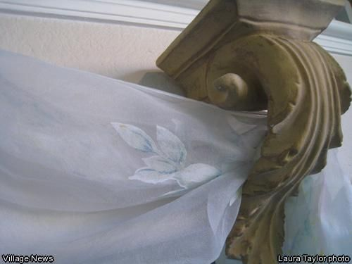 A sheer fabric can be hung from acanthus leaf bookends over a doorway to assist in a Mediterranean theme.