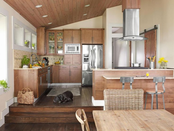 """The new space has a peninsula with a cooktop and space to sit, as well as marble countertops that Lisa Marie bought for a discount from a stone remnants distributor. The cabinets are made with affordable maple. """"If you're using wood like this, mix in a few glass-front doors so your cabinets don't look too heavy,"""" says Lisa Marie. The backsplash from Home Depot came in 1-foot-by-1-foot sheets of travertine and blue glass tiles in a block pattern. #Kitchen"""