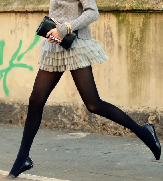 black tights, a chiffon mini skirt and a sweater of pale colours