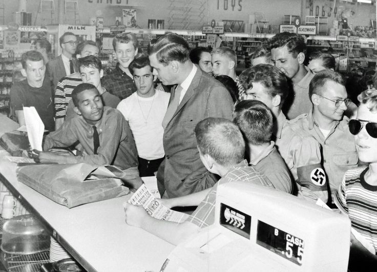 Dion Diamond [was one of a small interracial group that broke Jim Crow's back in the Washington, DC suburbs in 1960] sits calmly while Nazi Party chief George Lincoln Rockwell hurls racial insults during the Arlington, Virginia Drug Fair sit-in, 1960. (Photo by Gus Chinn, courtesy DC Public Library Washington Star Collection © Washington Post.)