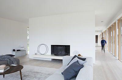 Obývací pokoj je od jídelny oddělen přepážkou, v níž je zabudovaný krb a která nesahá ani k jedné obvodové zdi domu.