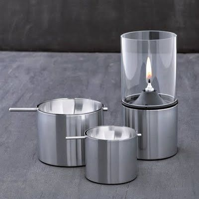 I've always had a soft spot for pure geometry in my environment, and like many am a sucker for the cold touch of stainless steel. Stelton, the Danish firm known for excellence in both since 1960, has thus been my go-to brand for tabletop accessories and these two products exemplify why. The Revolving Ashtray by Arne Jacobsen and Oil Lamp by Erik Magnussen optimize the functional possibilities of cylinders in ways that look as contemporary today as when designed (1970 and 2001, respectively)…
