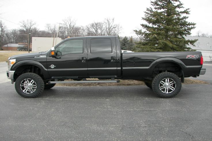 black long bed Ford F Series 4 x 4 truck