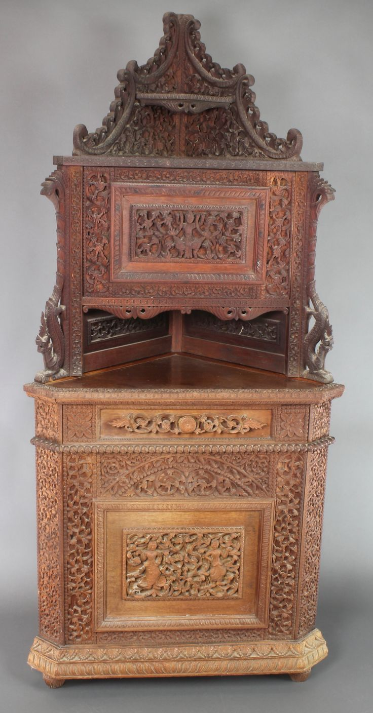 "Lot 1035,	A 19th Century carved Burmese hardwood corner cupboard, the upper section with pierced back fitted a cupboard above recess, the base fitted a cupboard enclosed by a panelled door 75""h x 35""w x 20""d sold for £560"