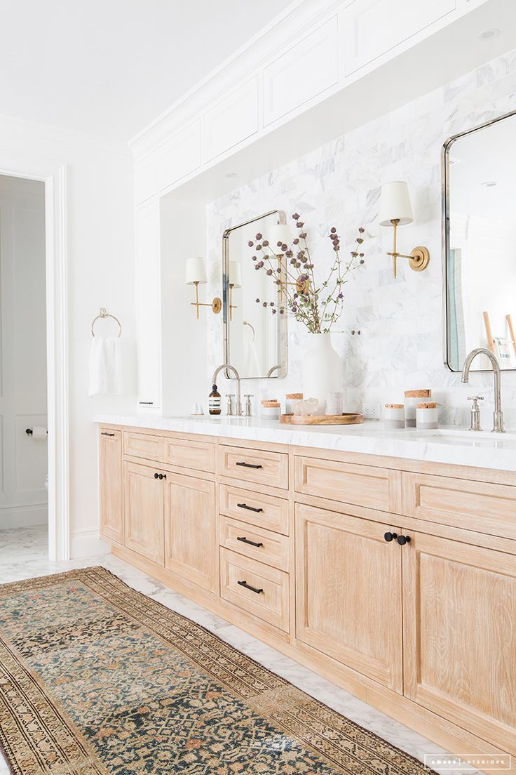 Bathroom design: whitewashed wood vanity with marble subway tile and brass accents/lighting.