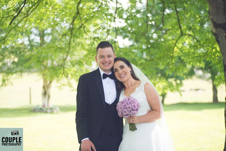 Bright, natural shot of the bride & groom shaded under a tree. Weddings at The Radisson Galway photographed by Couple Photography.