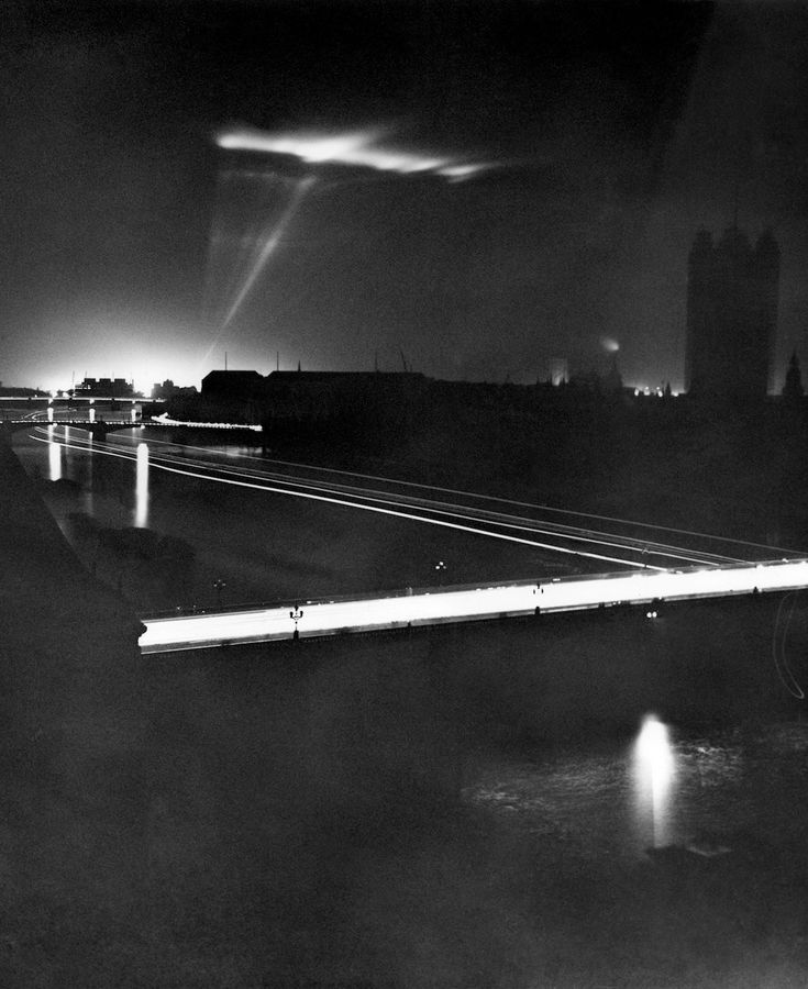 Aug. 11, 1939 A searchlight scans the sky above Westminster. Westminster Bridge in the foreground is a river of automobile light across the Thames, while the river itself looks like a modern highway with the tracks of passing river transport. This picture, like the other images of the Blackout in this selection, had a very long exposure time of up to 15 minutes. IMAGE: AP PHOTO