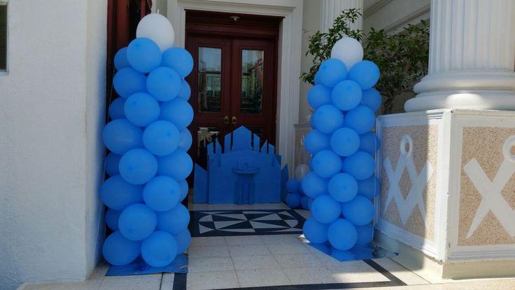 Dos torres de globos y la caja para regalos en forma del castillo de Frozen a la entrada del salon