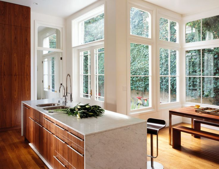 A dose or rich wood helps to ground this bright window-encased kitchen, by Nilus Designs.