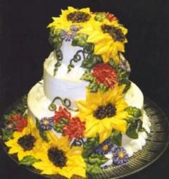 Gorgeous white wedding cake adorned with large yellow sunflowers, and smaller green leaves, red and purple flowers