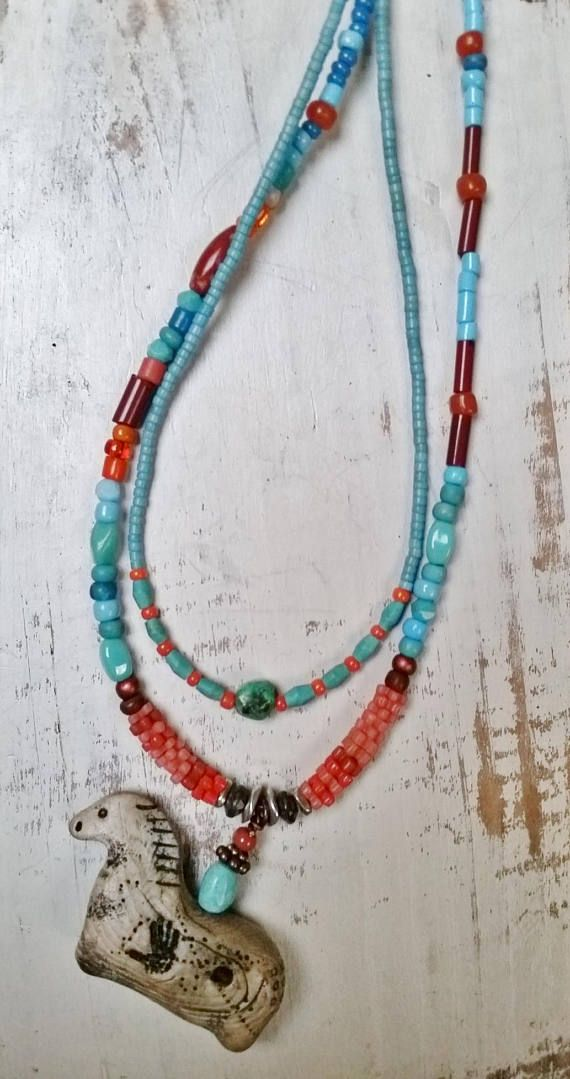 A long (30) two-strand colorful, eclectic necklace featuring antique trade beads, semiprecious stones, and my own handmade faux ivory horse artifact, inspired by the cave paintings of horses in the Lascaux Cave in France.  Each animal artifact has a story. They appear in my life, and then
