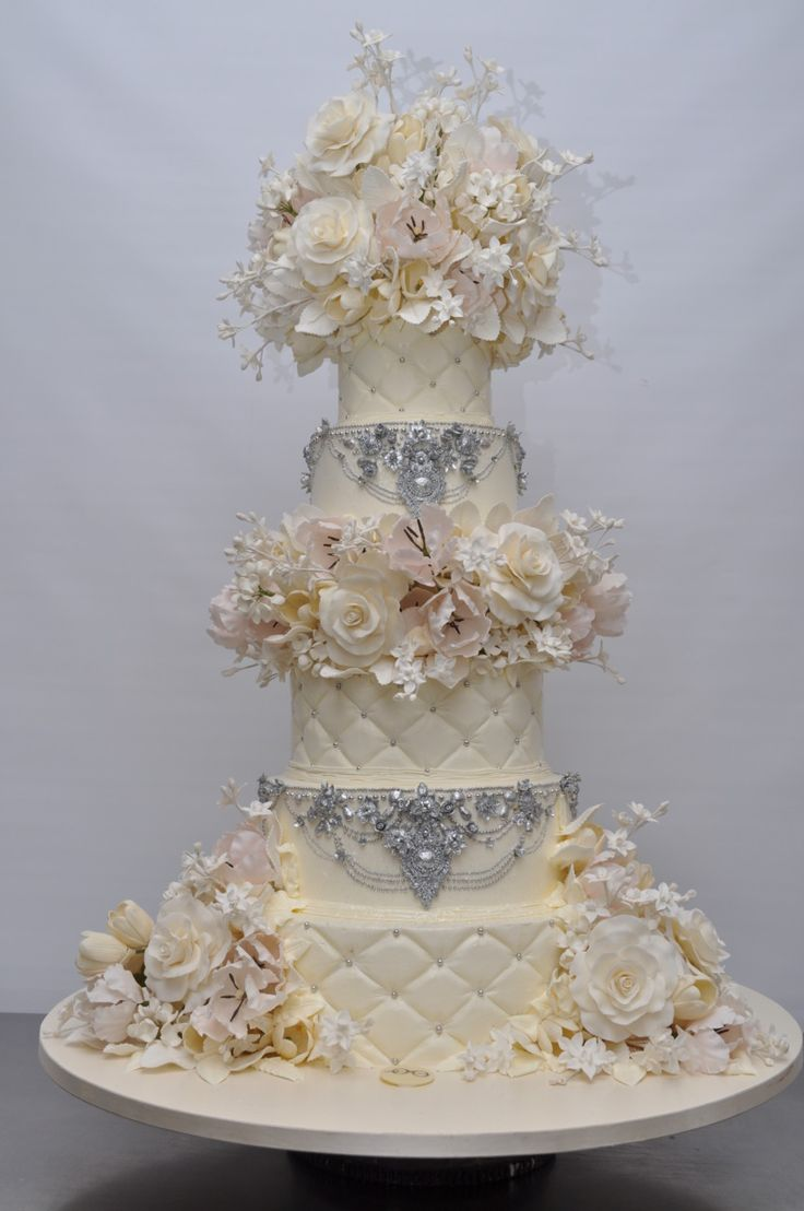 Elegant tall white wedding cake with a touch of glitz. By Sylvia Weinstock.