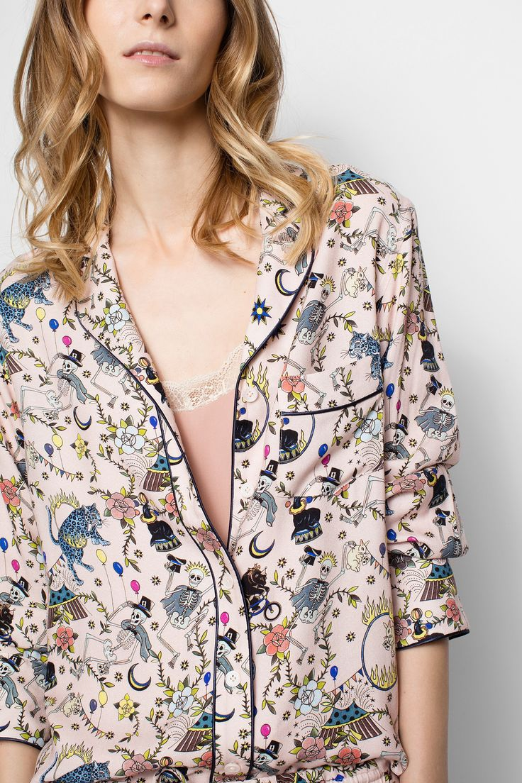 Zadig & Voltaire printed shirt, pyjama top-style, long sleeves, appliqué front pockets, decorated with satin piping, 100% viscose. The circus motif, a colorful mix of dancing skeletons, big tops and animals, is the product of an original collaboration with Brooklyn tattoo artist Virginia Elwood. This pyjama shirt transgresses norms when worn in town, with sleeves rolled up, jeans and a pair of studded ankle boots. Made in France, Italian fabric.
