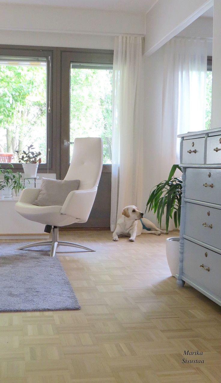 Vaalea, moderni olohuone. Valkoinen, harmaa, tammimosaiikkiparketti, nojatuoli, vanha lipasto. Grey livingroom