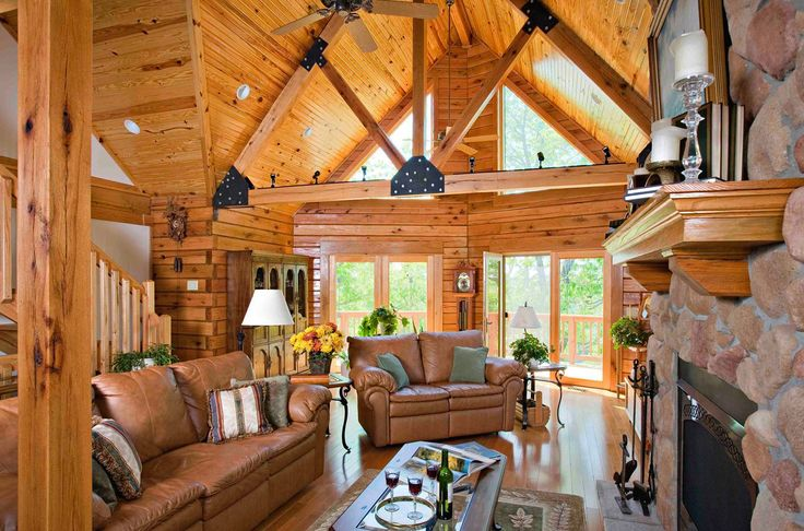 Quaker's Brighton Wood Clad Windows fill this living room by Gastineau Log Homes with gorgeous natural light.