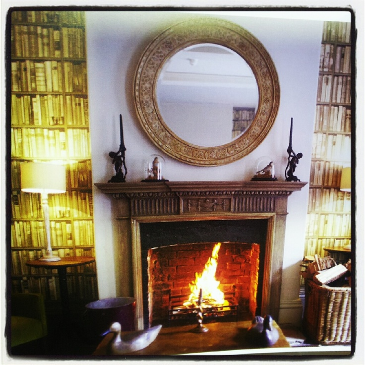 Fireplace with round circular mirror and Andrew Martin Bookshelf wallpaper.