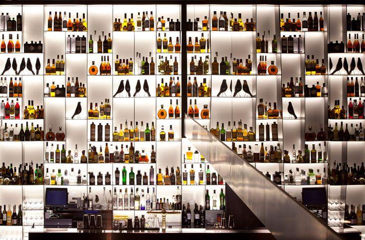 Piero Lissoni: Conservatorium Hotel, Amsterdam - wall of illuminated bottles and Eames house birds