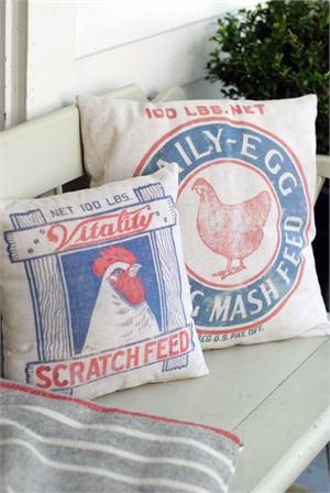 """Add a little rustic charm to your farmhouse decor with this Chicken Feed Sack Pillow Set. Inspired by vintage grain sacks used to store mash feed and scratch feed, these two pillows are printed on both sides. The colorful red and blue chicken feed supply logo appears against a tea-stained light oatmeal color fabric. The backsides display company logos with feed ingredients. The large Mash Feed Pillow is 16"""" Square and the small Scratch Feed Pillow is 12"""" Square. Set of two. Cotton/Polyester"""