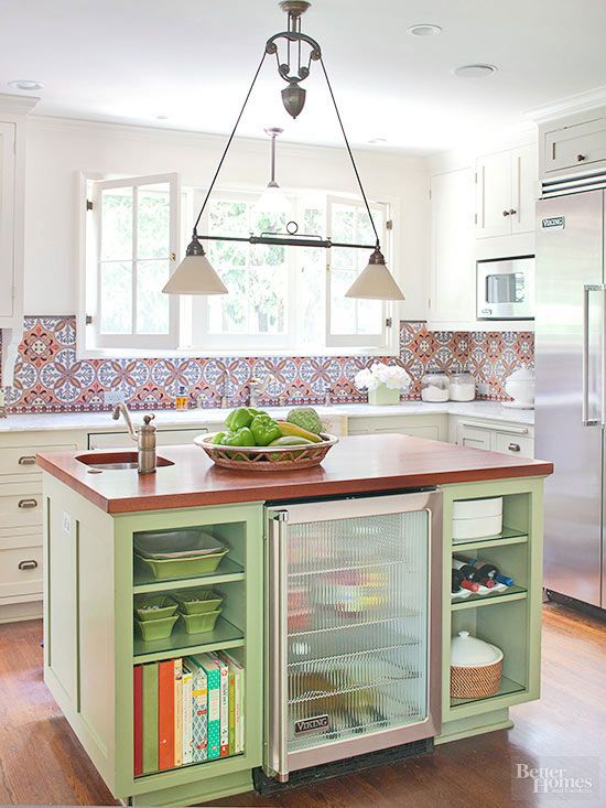 The island's mahogany countertop adds warmth and serves as a refreshing counterpoint to the perimeter's cool marble surfaces. The lively green base cabinetry complements the medley of warm colors seen on the backsplash./