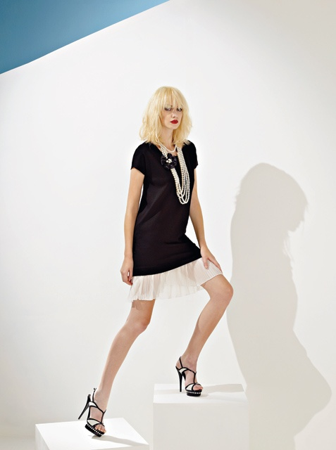 Black and white mini dress with attached pleated white mini skirt. Pearl necklace with black camelia also from Anna Rachele S/S '13 collection