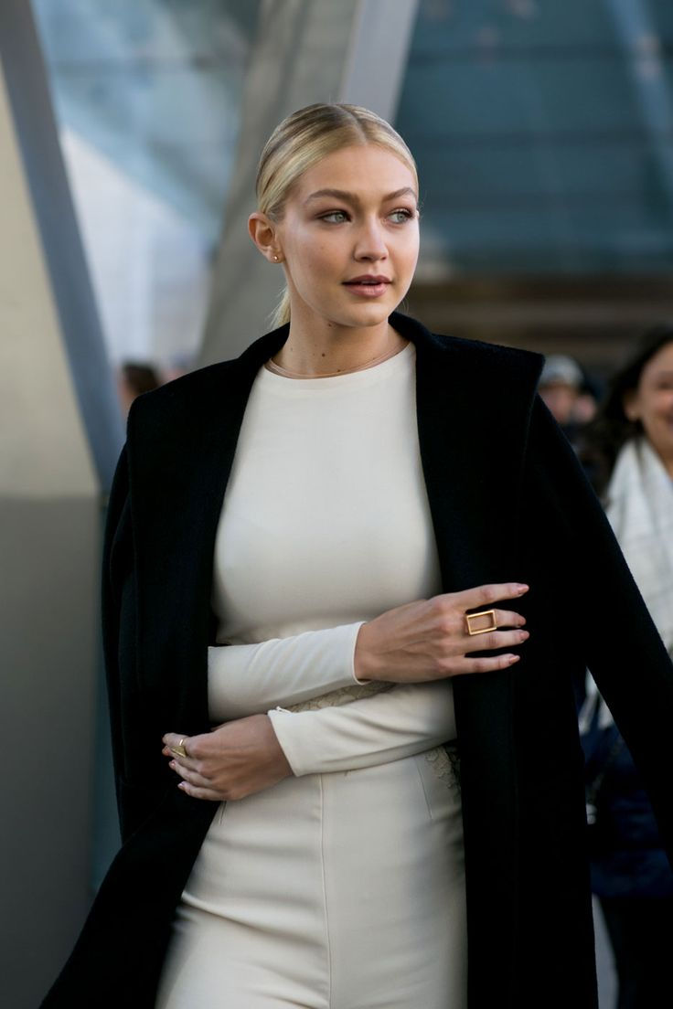 Incredible Model Street Style Outfits From New York Fashion Week - Gigi Hadid wearing a winter white jumpsuit + black overcoat