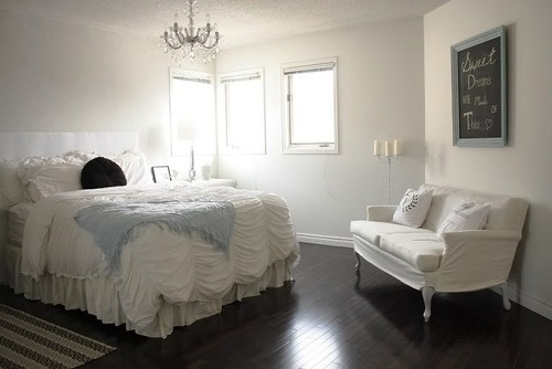 White bedroom with a touch of blue.  Chalkboard above soft bench.