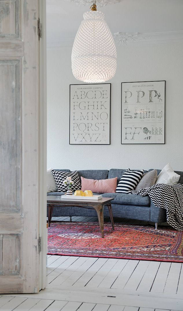 Grey couch, white floor boards, accents of pink, kelim rug