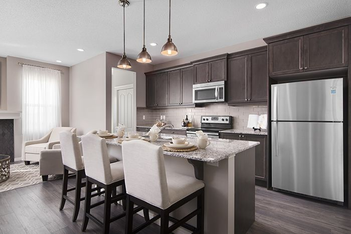 Kitchen with central island  in the Wysteria showhome in the community of Redstone in northeast Calgary