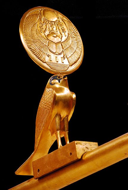 Detail of Tut's ceremonial chariot. The falcon Horus wears the solar disk on which is engraved the winged scarab, symbol of the rising sun and resurrection and a sun,( Amarna period), giver of life (hieroglyph: The Key of Life)