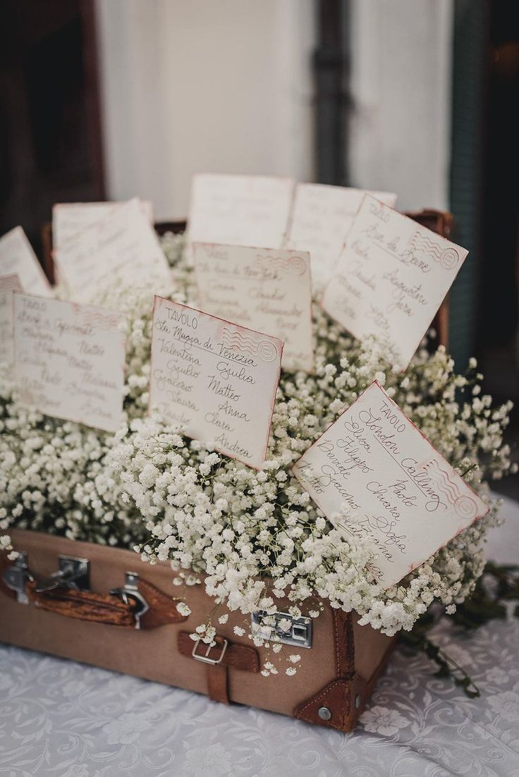 seating chart in a vintage suitcase filled with gypsophila